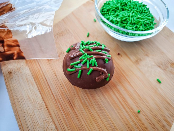 one bomb topped with green sprinkles sitting on a wooden board next to a small glass bowl filled with sprinkles