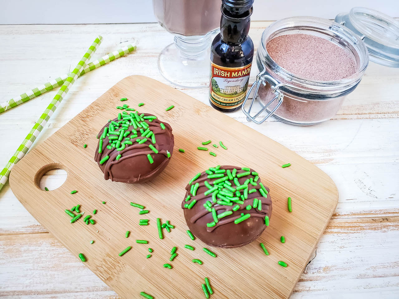 two hot cocoa bombs sitting on a wood cutting board with green sprinkles. A cup of hot cocoa, a bottle of Irish cream, and a glass jar of hot cocoa mix in the background, with two green striped straws