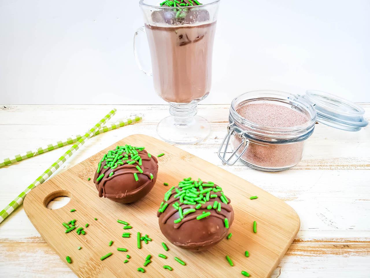 two hot cocoa bombs sitting on a wood cutting board with green sprinkles. A cup of hot cocoa and a glass jar of hot cocoa mix in the background, with two green striped straws