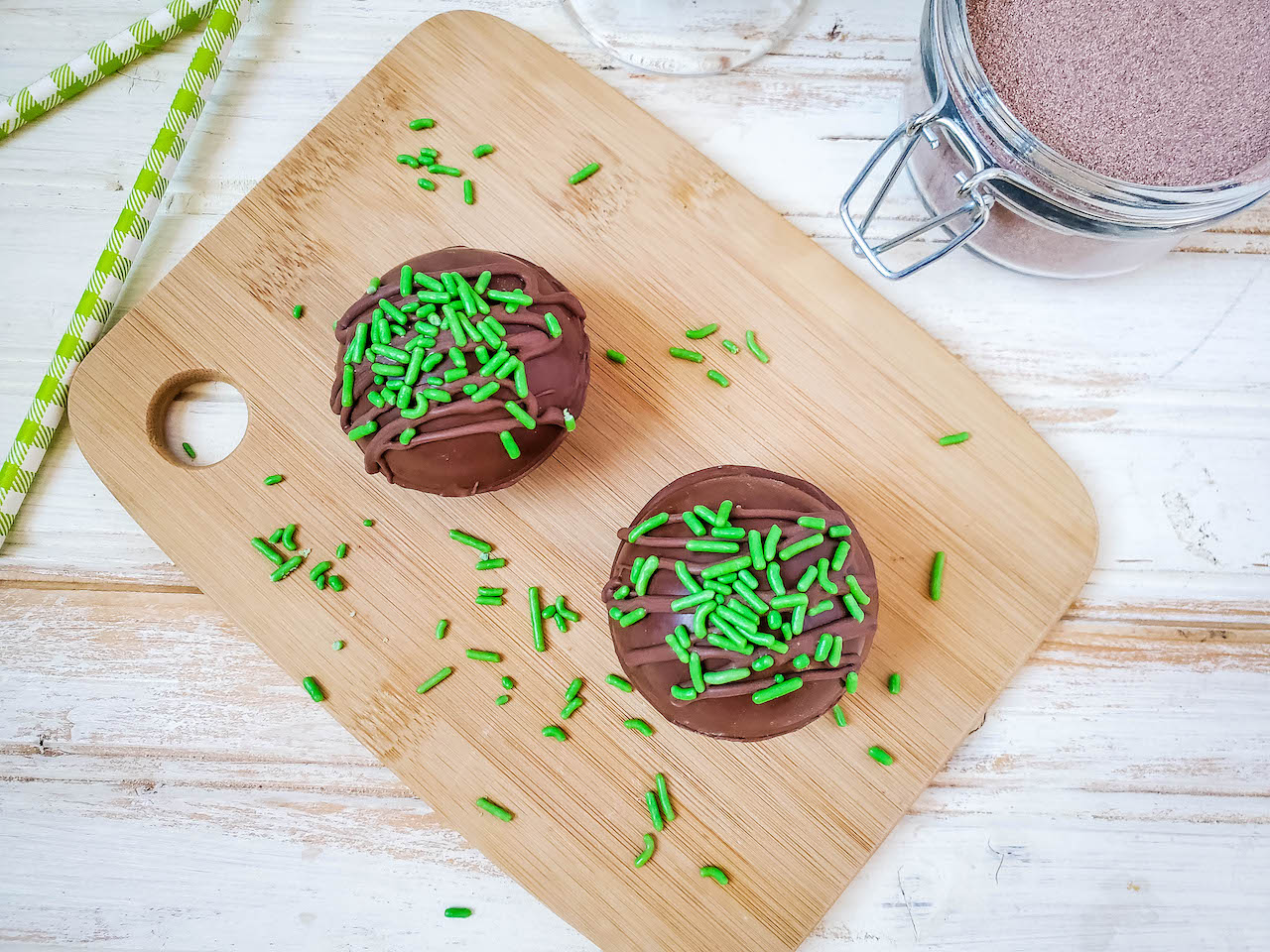 two cocoa bombs sitting on a wooden board covered with green sprinkles. Green stripped straws and a jar of cocoa mix in the background