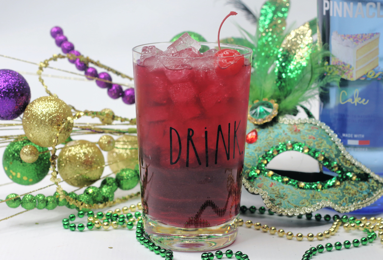 a clear glass filled with King Cake Cocktail sitting in front of beads, a mask and other Mardi Gras decorations