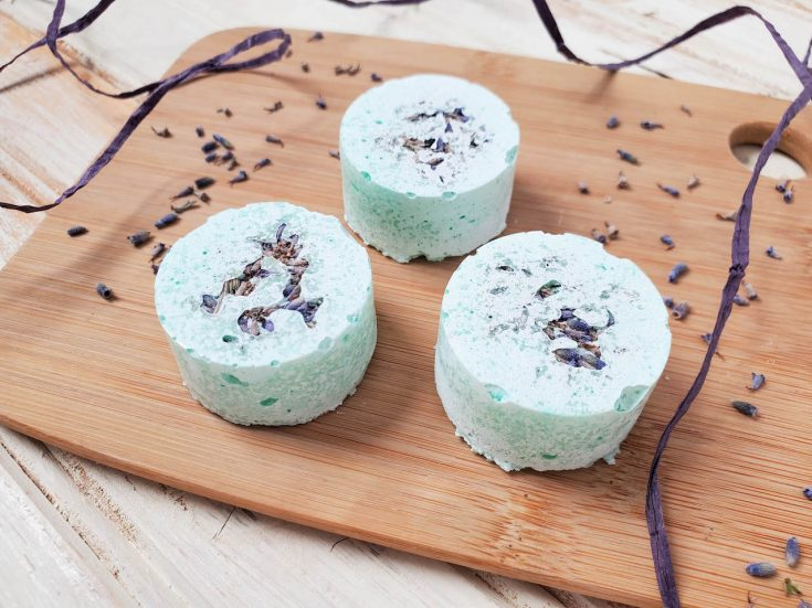three diy shower steamers sitting on a wood board with tea tree leaves surrounding