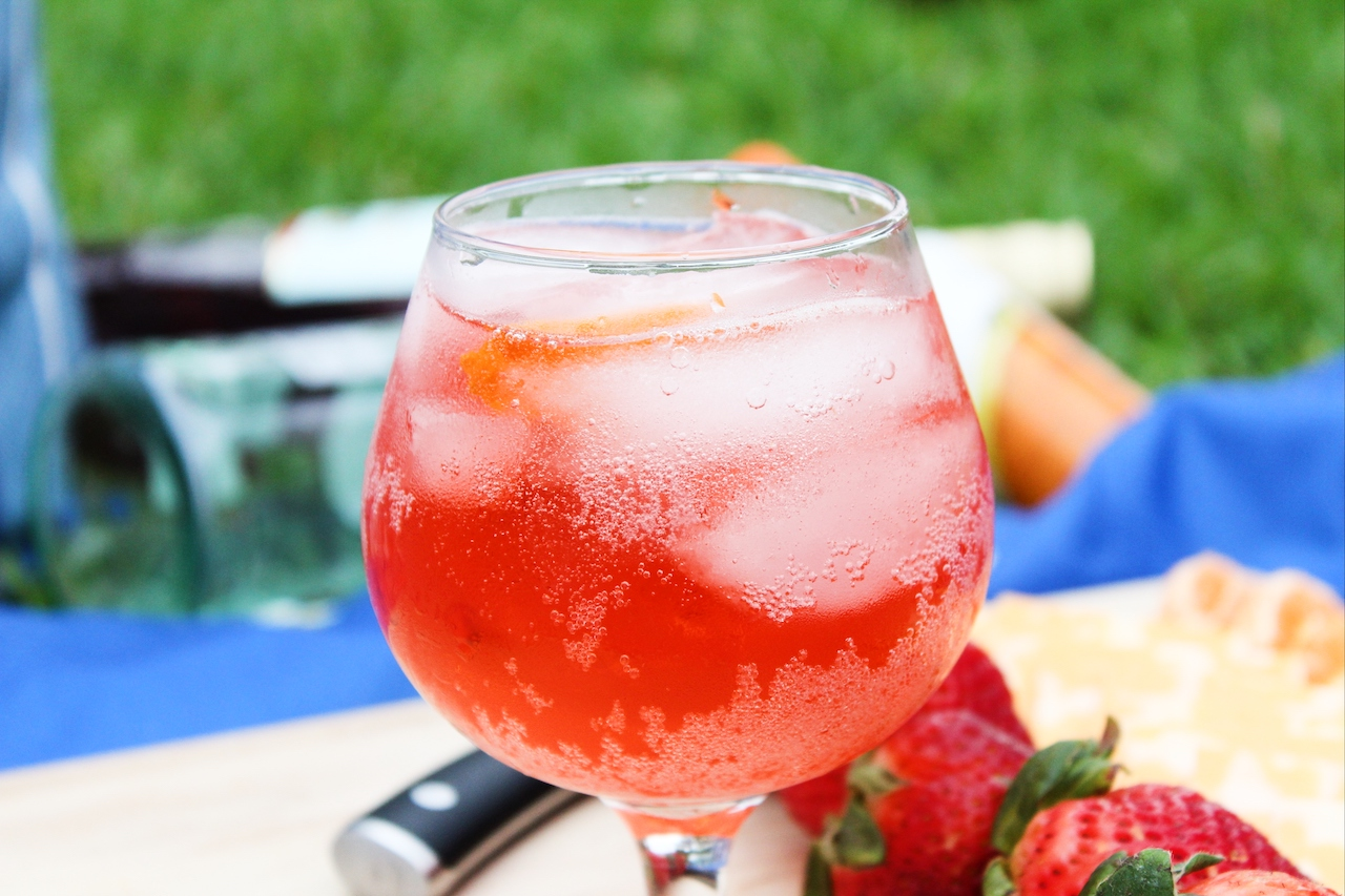 unclose of cocktail in glass with ice sitting outside. Strawberries next to glass