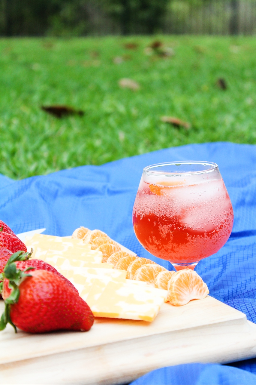 glass of picnic punch sitting on a blue blanket outside with a Charcuterie board