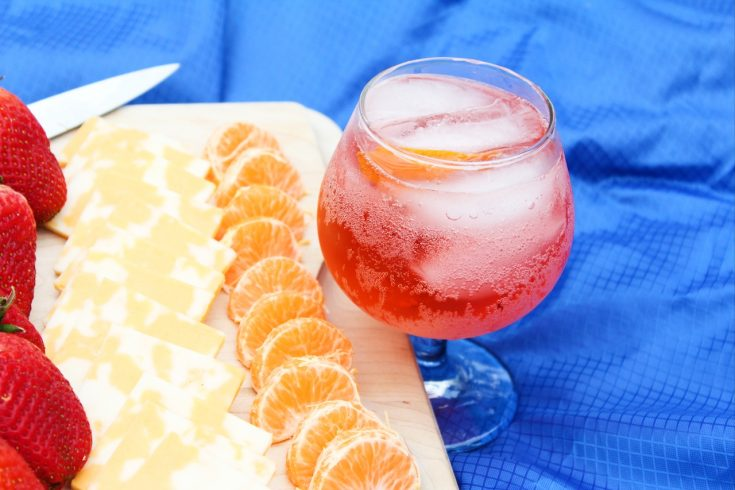 an easy summer cocktail in a glass sitting on a blue cloth next to a cutting board and knife with orange slices, cheese slices, and strawberries